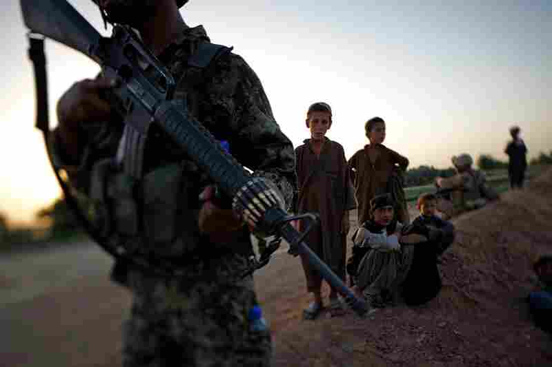 Local children watch, fascinated, as an Afghan National Army soldier walks along a dirt embankment during a joint patrol with the 2/8 Marines. The soldiers stop and search all the locals who pass by, looking for weapons and illegal goods, mainly drugs.