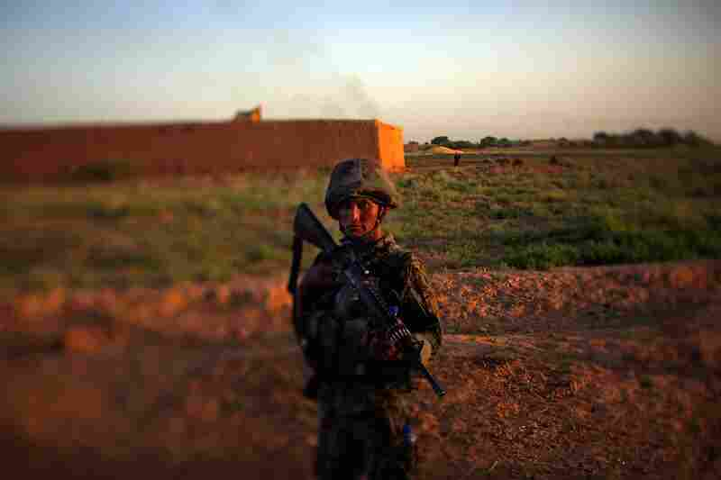 An Afghan National Army soldier holds a security position in front of a local farmhouse during a joint patrol with the Marines.