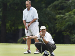 President Barack Obama points to Vice President Joe Biden's putt as he and House Speaker John Boehner (R-Ohio), are on the first hole during their golf game at Andrews Air Force Base, Md., June 18, 2011.