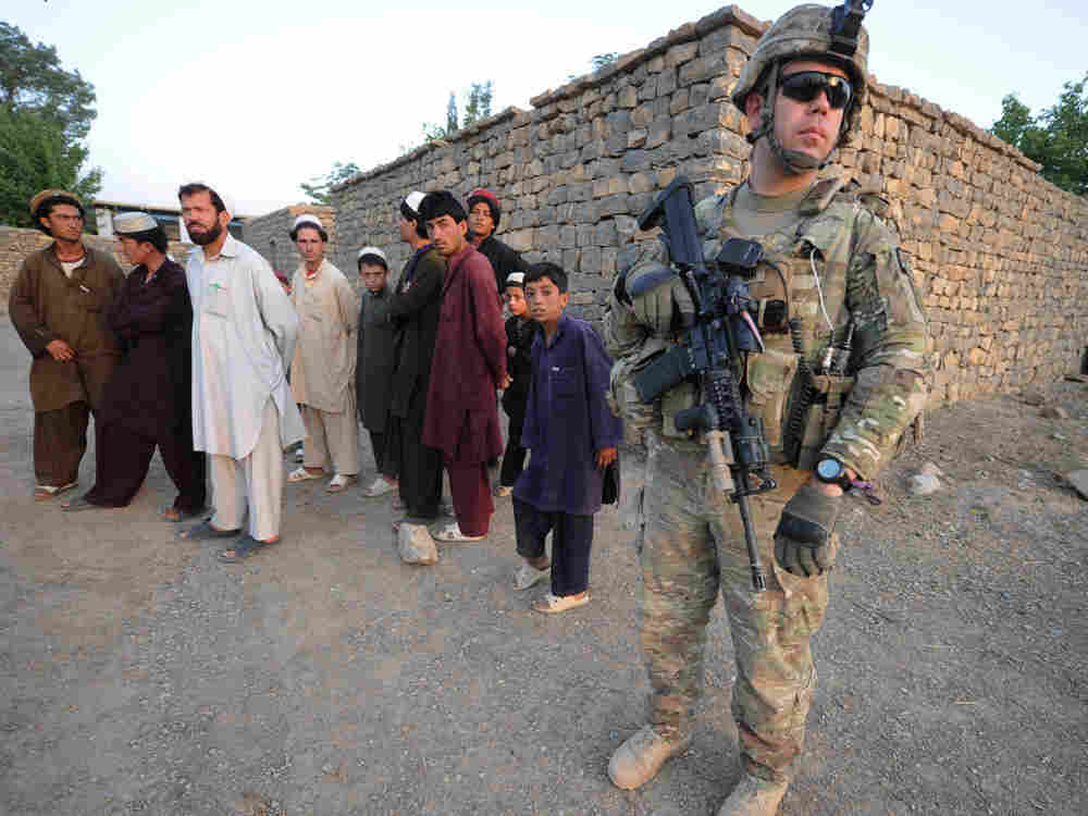 A US soldier of the Viper Company (Bravo), 1-26 Infantry, stands next to Afghans during a home to home search in the Sabari village, in the Khost province of eastern Afghanistan, on June 19, 2011.  In our first hour, military experts talk about a possible time line for bringing troops home from Afghanistan.