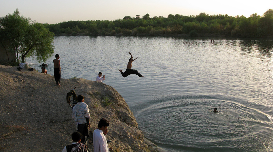 Men in Lashkar Gah jump into the Helmand River to beat the 120 degree heat of the Afghan summer.