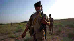 Isutalah of the Interim Security for Critical Infrastructure force on foot patrol in northern Marjah with Marines of Golf Company, 2nd Battalion, 8th Regiment.