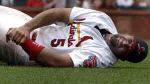 St. Louis Cardinals first baseman Albert Pujols grabs his left wrist after being injured on a play at first base during a game against the Kansas City Royals Sunday, June 19, 2011, in St. Louis.