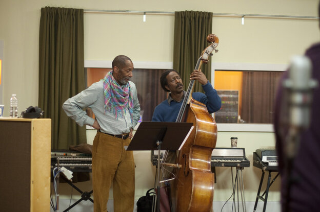 Ron Carter (left, as himself) looks on as Albert Lambreaux (Clarke Peters) attempts to show him a thing or two on bass, in Treme.