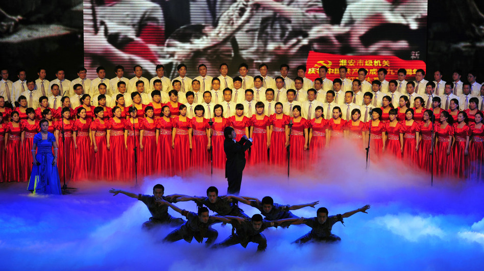 "Officers from Huaian city perform patriotic ""red songs"" at the Huaian Great Hall of the People to mark the 90th anniversary of the founding of the Communist Party of China. (Getty Images)"