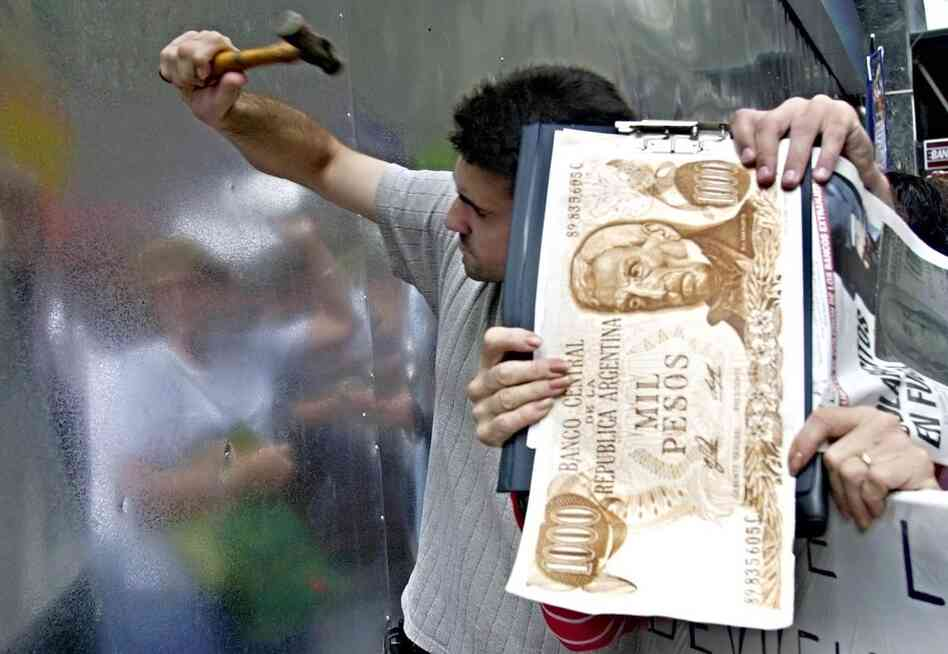 ARGENTINA, defaulted in 2001. Argentines try to break down a metal wall at a bank in Buenos Aires in 2002 to protest the government-imposed blockade that had prevented access to their savings since the beginning of December 2001.