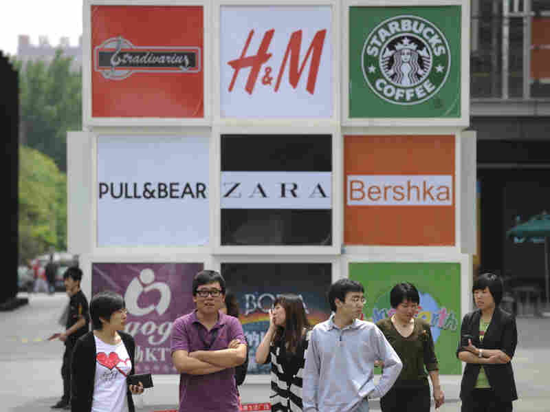 Commuters stand in front of billboards outside a shopping mall in Beijing. Brand logos are a common sight in China — but not for homegrown companies.