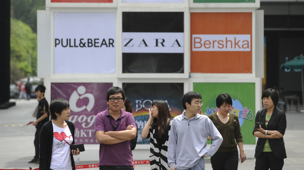 Commuters stand in front of billboards outside a shopping mall in Beijing. Brand logos are a common sight in China — but not for homegrown companies. (Getty Images)