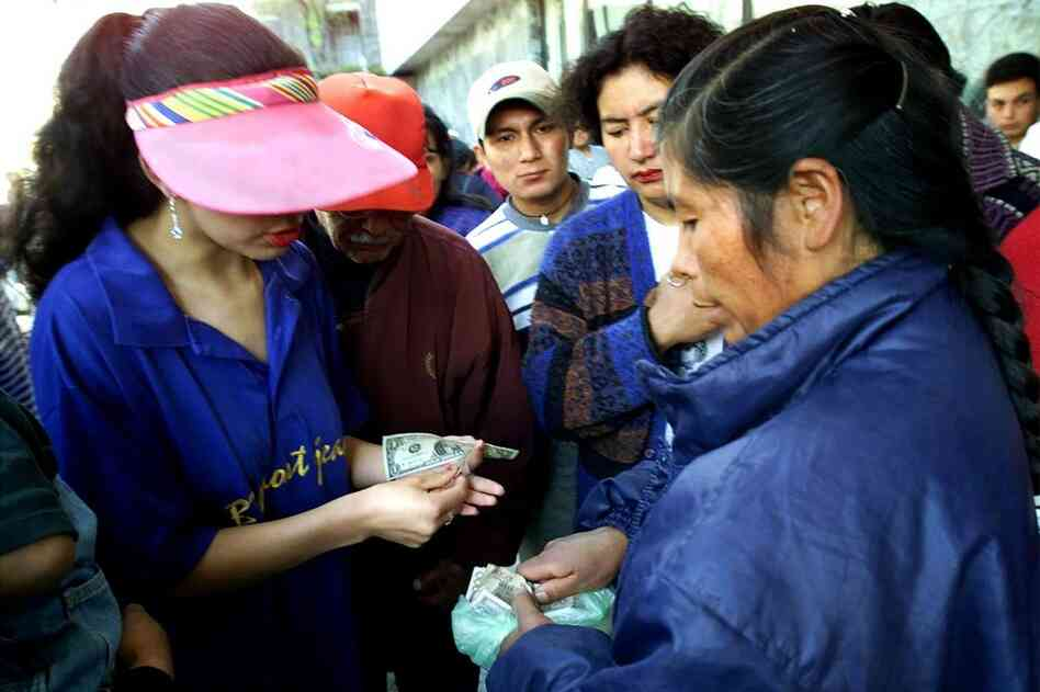 ECUADOR, defaulted in 1999, 2008.  A woman exchanges Ecuadoran sucres for U.S. dollars at the Central bank in Quito in 2000. Ecuador switched to dollars after its c