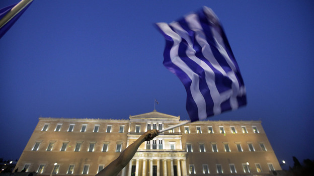 A protester waves the national flag of Greece during a demonstration Tuesday at Athens' Syntagma square in front of the Greek Parliament. Demonstrators have been camped outside Parliament since May 25.