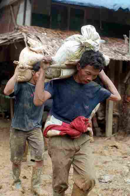 INDONESIA, defaulted in 1998. Indonesian miners carry bags of mud to be filtered for gold at the Aneka Tambang gold mining site in 1999. Hundreds of gold miners had been digging at the state-owned mining site without a permit since an economic crisis hit the country in 1997 and again the following year.