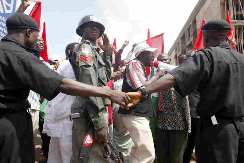 NIGERIA, defaulted in 2002. Police officers mount a barricade at the Labour Secretariat in Abuja to stop workers from marching in the street in 2004 amid continued economic woes. Nigerian trade unionists had gathered in the capital to protest rising fuel prices and mobilize support for an imminent general strike.