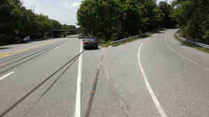 A police car sits near skid marks leading to where Ryan Dunn's Porsche went off the road Monday in West Chester, Pa.