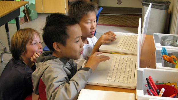 Fifth-graders (from left) Reese Toomre, Lucas Nguyen and Michael An race through the Khan  Academy's Trigonometry Challenge. The program allows more advanced students to  move ahead, while other students can proceed at their own pace. (NPR)