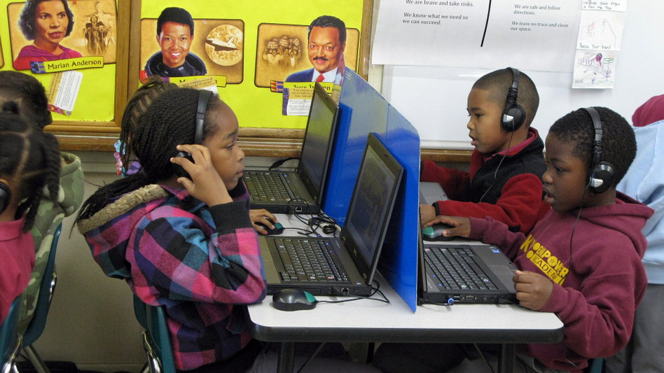 Kindergartners at KIPP Empower Academy in South Los Angeles work on laptops while in another corner of the room, a group of students do an activity with a teacher.