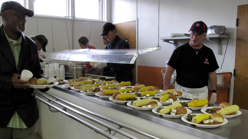 Steven White (right) helps serve dinner at the Salvation Army soup kitchen. (NPR)