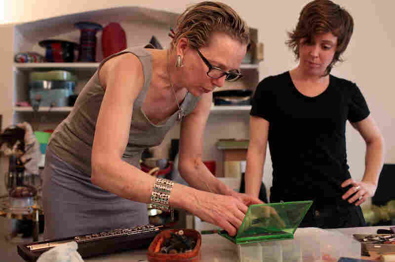 Anne Pollock, New York's go-to person for flute repairs, makes adjustments to the gold head joint of Chase's instrument while she looks on.