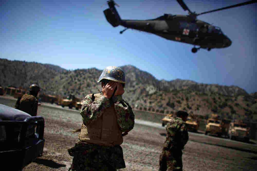 A US Army medevac Blackhawk helicopter lifts off carrying a critically injured Afghan National Army soldier as his fellow soldiers watch at Combat Outpost Wilderness in Paktia provence, eastern Afghanistan. The ANA soldier was struck in the head with shrapnel during an enemy mortar barrage at the remote base in the mountains of eastern Afghanistan.