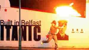 A masked rioter throws a petrol bomb in Belfast on Tuesday (June 21, 2011).