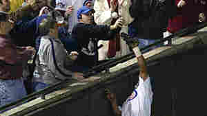 Fans and outfielder Moises Alou of the Chicago Cubs reach for a fly ball hit by Luis Castillo of the Florida Marlins in 2003.