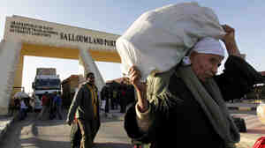 Egyptians who fled fighting in Libya carry their belongings at the Egyptian-Libyan border in Salloum, Egypt. The International Organization for Migration estimates that more than 105,000 Egyptians have returned from Libya.