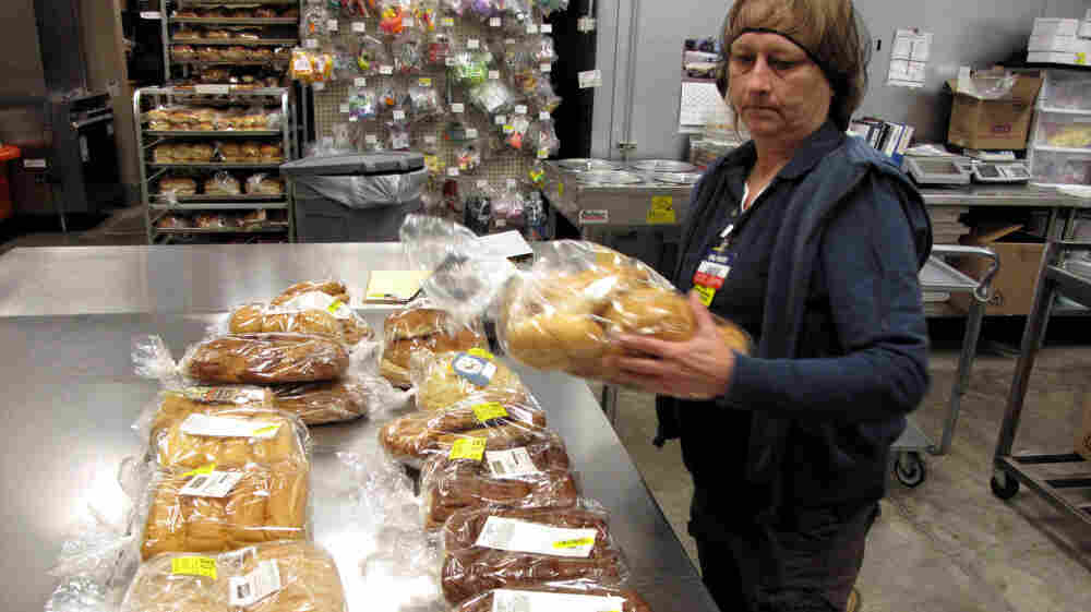 Jackie Barnes, a Walmart employee, packs bread for donation. Last year, the company pledged to donate $2 billion in food and other aid to food banks  over five years, the largest donation of its kind.