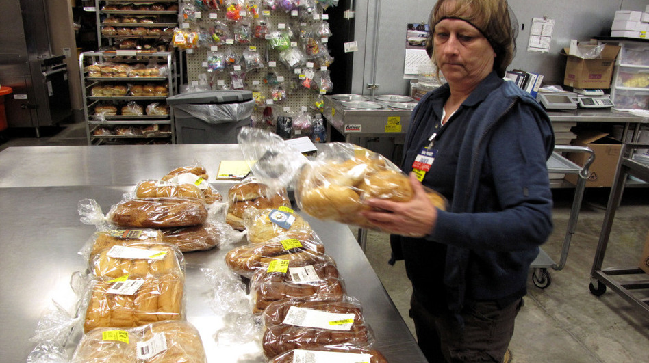 Jackie Barnes, a Walmart employee, packs bread for donation. Last year, the company pledged to donate $2 billion in food and other aid to food banks  over five years, the largest donation of its kind. (NPR)