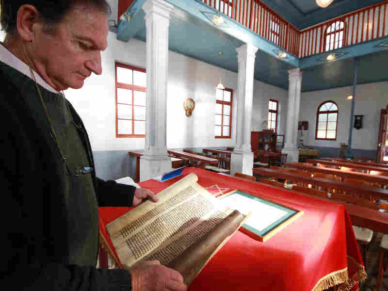 Abraham Kreiserman, the president of the Jewish community of Villa Clara, shows a portion of a Torah scroll at Beth Iacob Synagogue in Villa Clara.