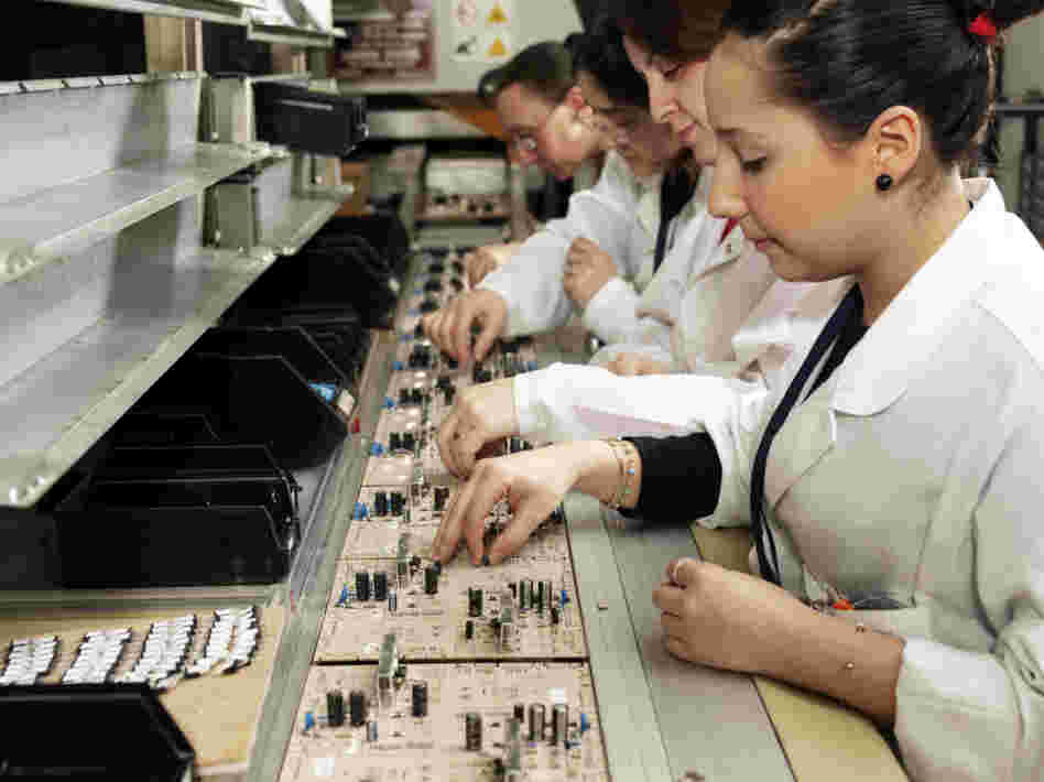 Workers with circuit boards on a production line.