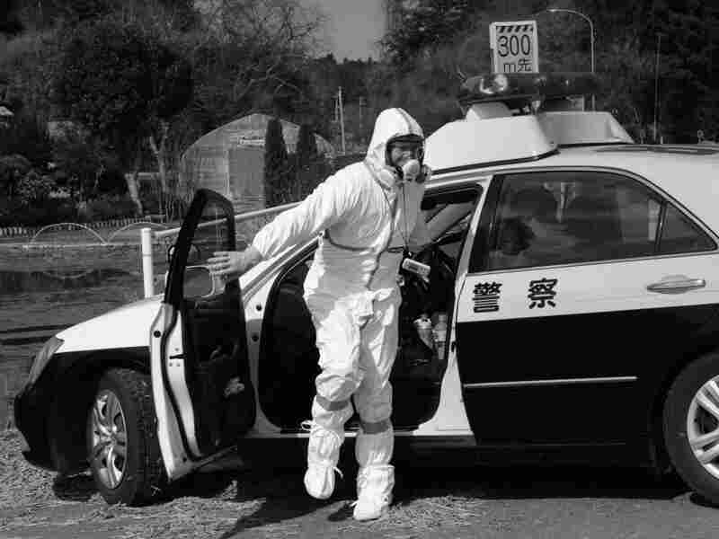 Police in a hazmat suit near the damaged Japanese nuclear plant.