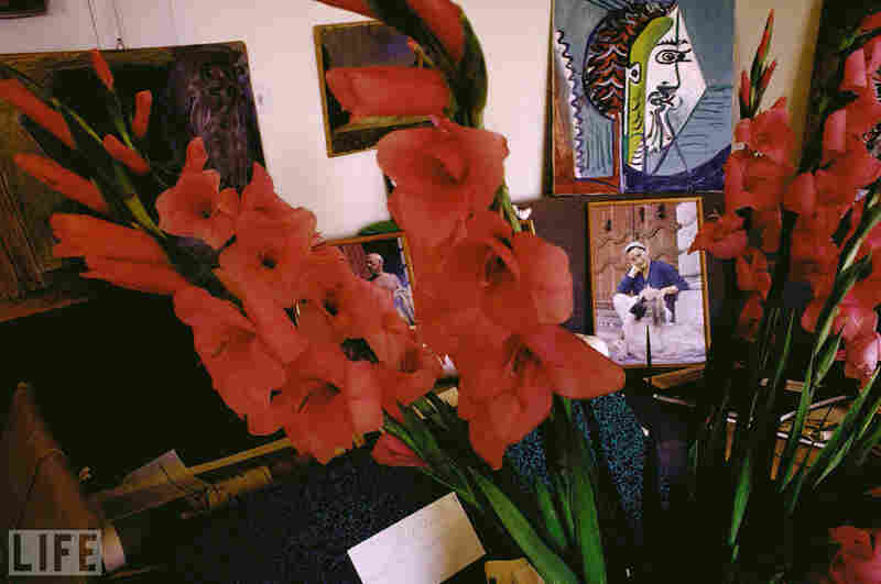 Inside the drawing room of his home in Mougins, flowers and paintings surround two portraits taken by David Douglas Duncan.