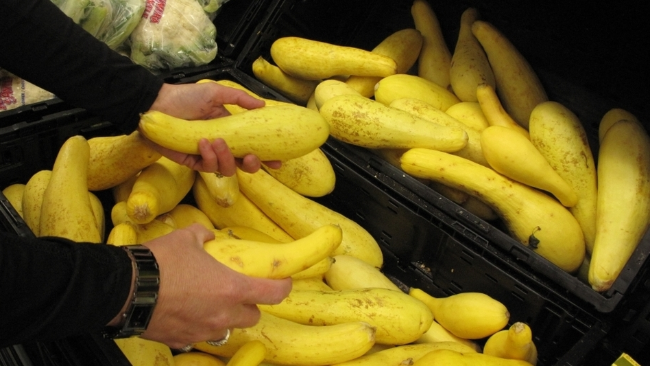 Walmart store manager Emily Bowman notices some yellow squash with brown spots — and takes about 40 off the shelves and puts them on a donation cart. (NPR)