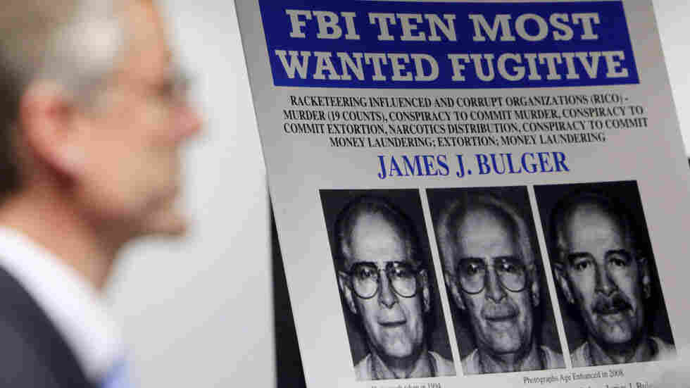 """FBI special agent Richard Deslauriers speaks Monday during a news conference next to a poster featuring fugitive James """"Whitey"""" Bulger at the FBI field office in Boston."""