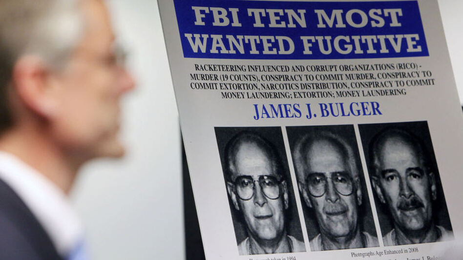 "FBI special agent Richard Deslauriers speaks Monday during a news conference next to a poster featuring fugitive James ""Whitey"" Bulger at the FBI field office in Boston. (Michael Dwyer/AP)"