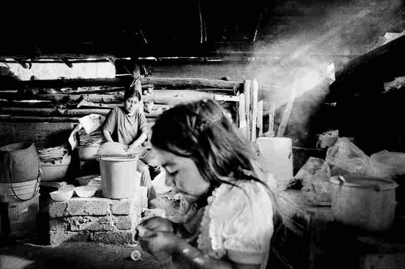 A woman makes tortillas on an indoor fire while her daughter plays nearby.
