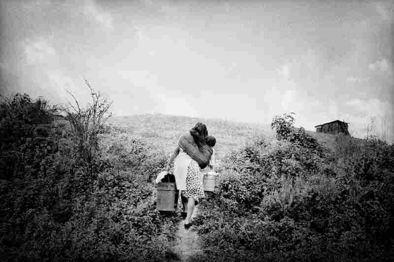 A woman returns home laden with her infant and household supplies.