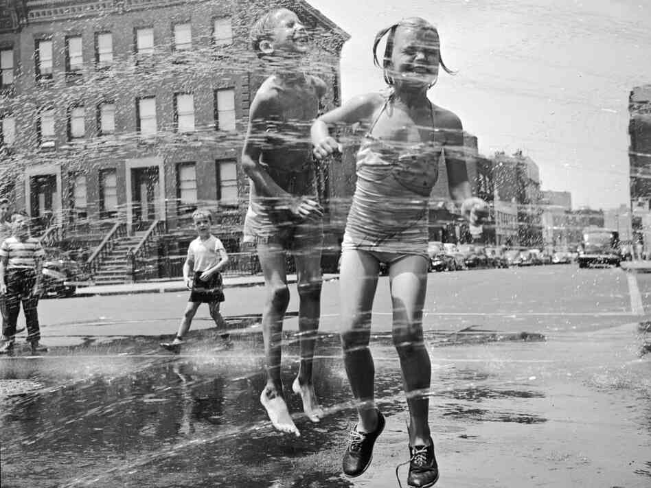 Two children jumping through a water hydrant's shower on a New York street. They have come from a neighbouring co-educational playgroup organised by the city's Police Department.  (Photo by Orlando/Getty Images)