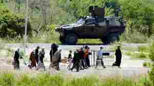 Syrian refugees pass a Turkish military vehicle as they cross into  Turkey near the town border of Guvecci in Hatay province on Thursday.