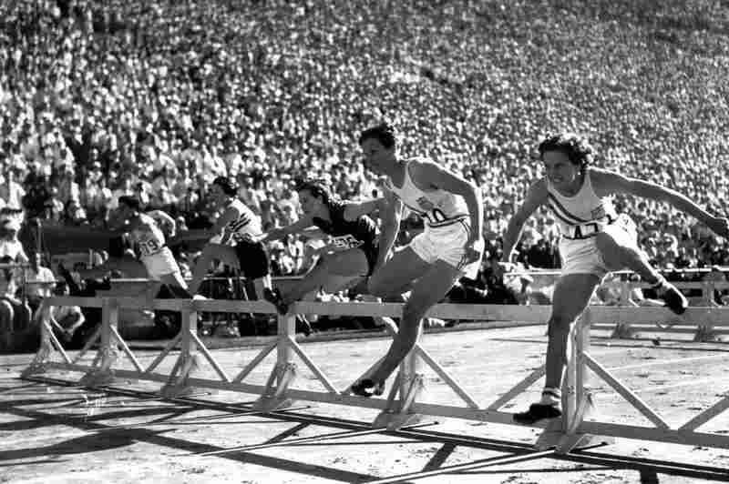 """Mildred """"Babe"""" Didrikson, one of the most versatile athletes of all time, first received attention as a star in basketball and track and field. Here, Didrikson (second from right) pulls ahead of teammate Evelyne Hall (far right) to win the women's 80-meter hurdles at the 1932 Summer Olympics in Los Angeles."""