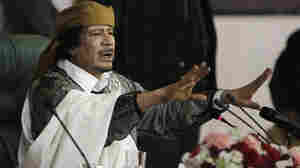 Libyan Leader Moammar Gadhafi gestures to supporters in March as he speaks in Tripoli, Libya. The International Criminal Court issued arrest warrants Monday for Gadhafi, his son and his intelligence chief for crimes against humanity in the early days of their struggle to cling to power.