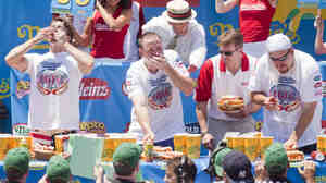 Competitive eaters down their frankfurters during the 2010 Nathan's Famous Fourth of July International Hot Dog Eating Contest at the original Nathan's Famous on Coney Island.