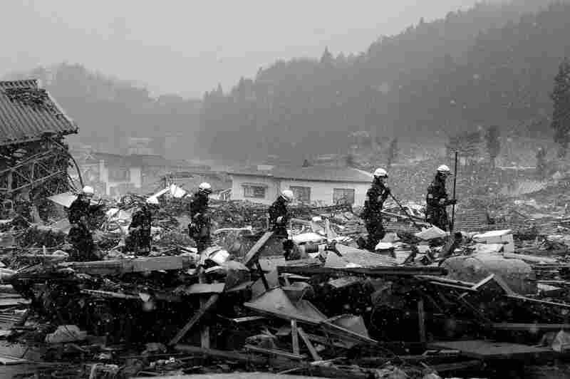 Soldiers look through wreckage in the town of Shinchi, Fukushima prefecture, following the tsunami.