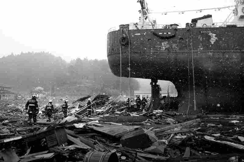 Rescue workers amid a sea of debris in Kesennuma, where enormous ships were grounded by the tsunami.