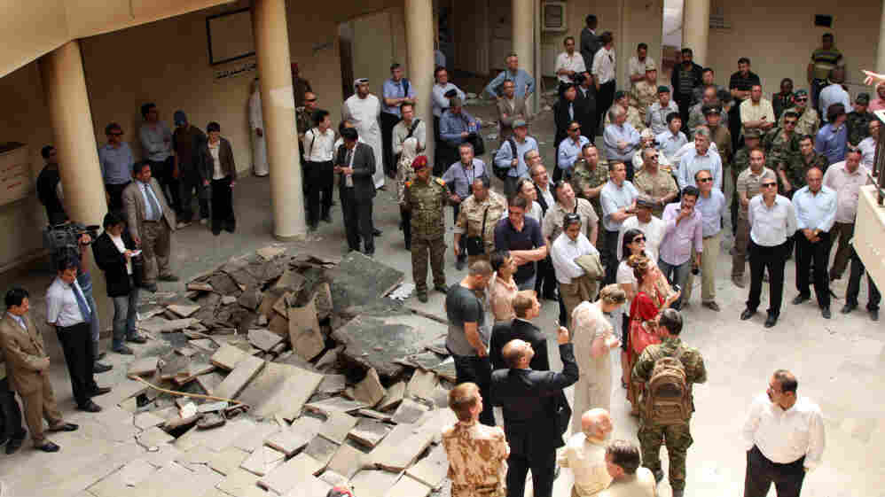 In this photo taken during a government-organized tour June 20, foreign diplomats and members of the media  stand inside the damaged court building  in Jisr al-Shughour, Syria, where authorities say armed groups killed more than 100 security personnel two weeks ago.