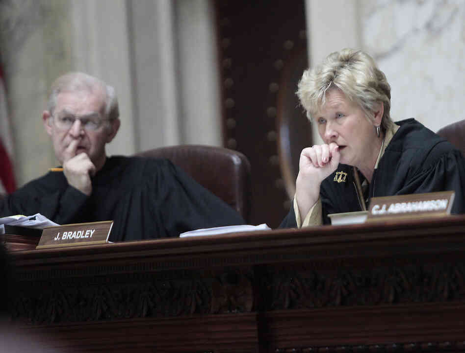 Wisconsin Supreme Court Justices David T. Prosser, Jr. and Ann Walsh Bradley consider oral arguments during a hearing regarding the state's budget bill at the