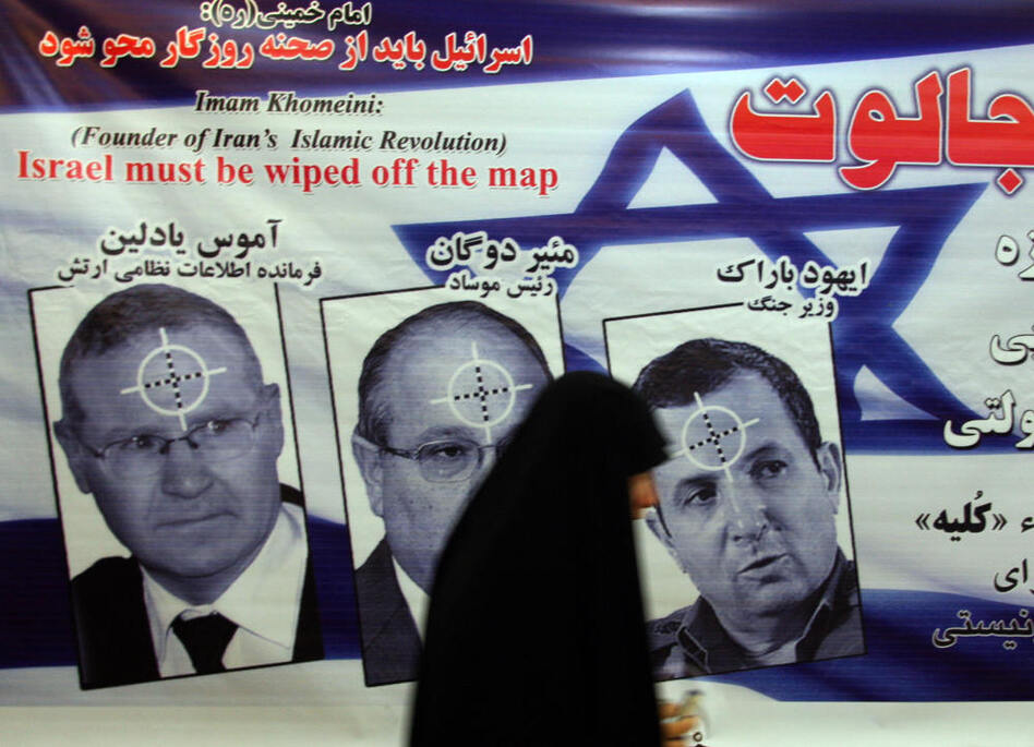 An Iranian woman walks past a poster featuring portraits of Israeli military intelligence chief Gen. Amos Yedlin, Dagan and Defense Minister Ehud Barak during an anti-Israel ceremony in Tehran in 2008.