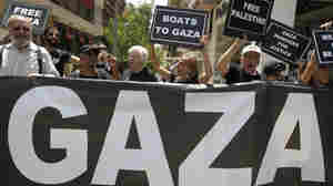 U.S. activists chant slogans as they hold placards after a news conference in Athens, Greece, about an international flotilla to blockade Gaza.