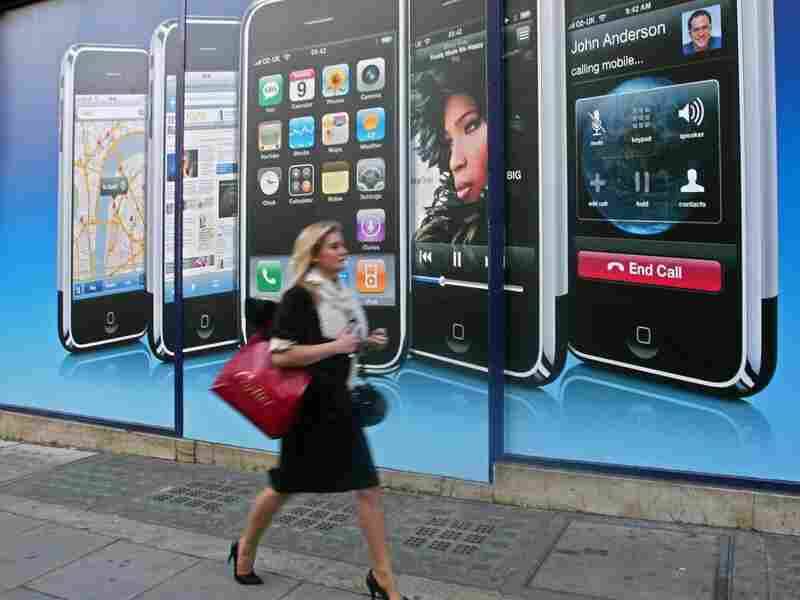 A woman walks by a new Apple location in London. Chen says the iPhone's reach has extended beyond the gadget market to impact all areas of our lives.
