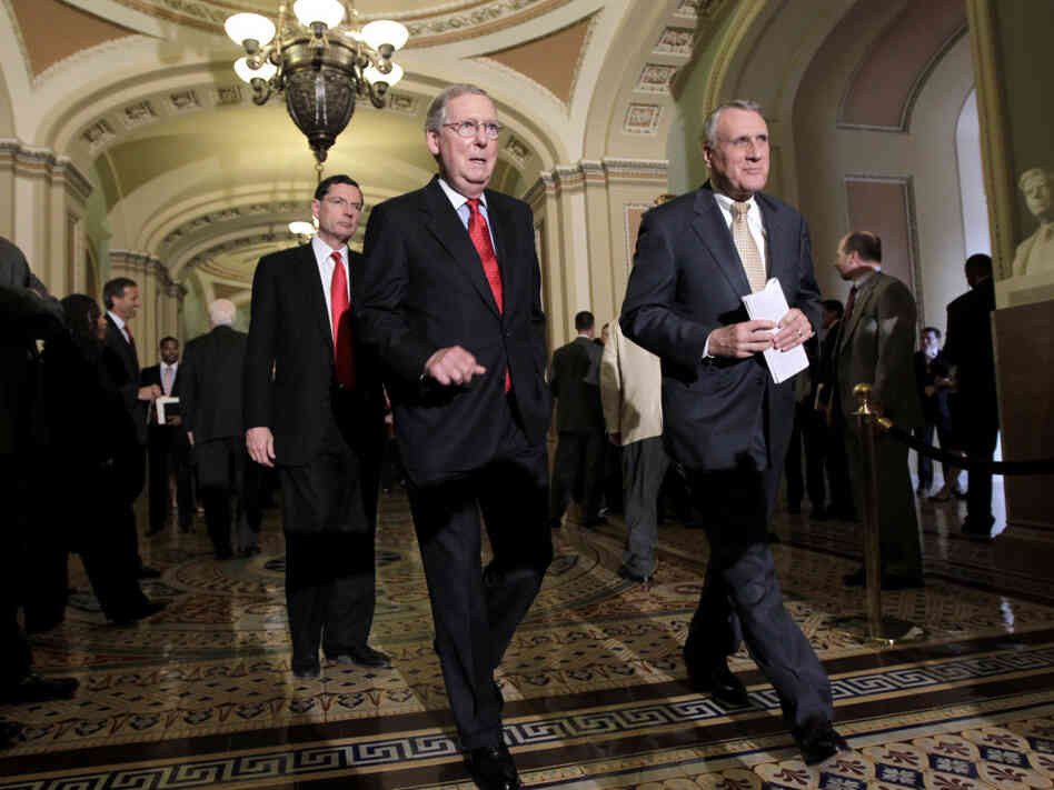 Senate Minority Leader Mitch McConnell (l) with Minority Whip Jon Kyl and Sen. John Barrasso   arrives to speak with reporters, June 28, 2011.