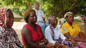 Cassimo Bique, an OB-GYN, sits with traditional birth attendants in Mozambique. Bique is an advocat
